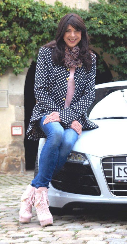 pretty woman sitting on car