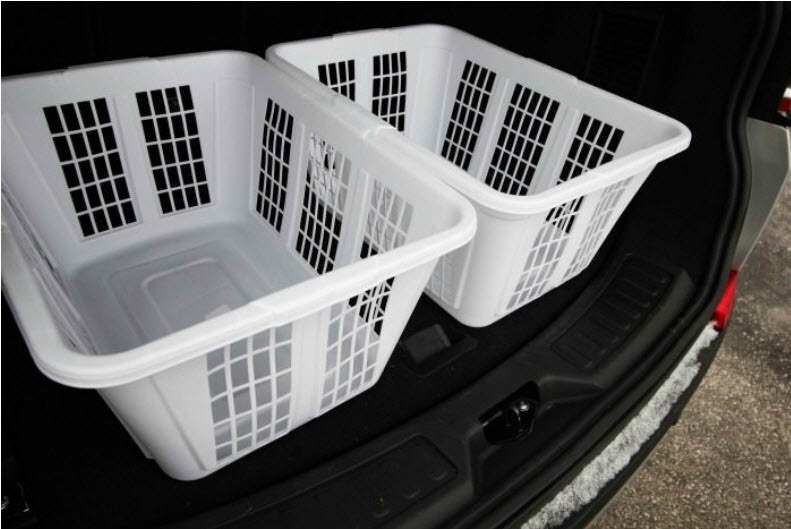 Two white laundry baskets sitting in the trunk of a car