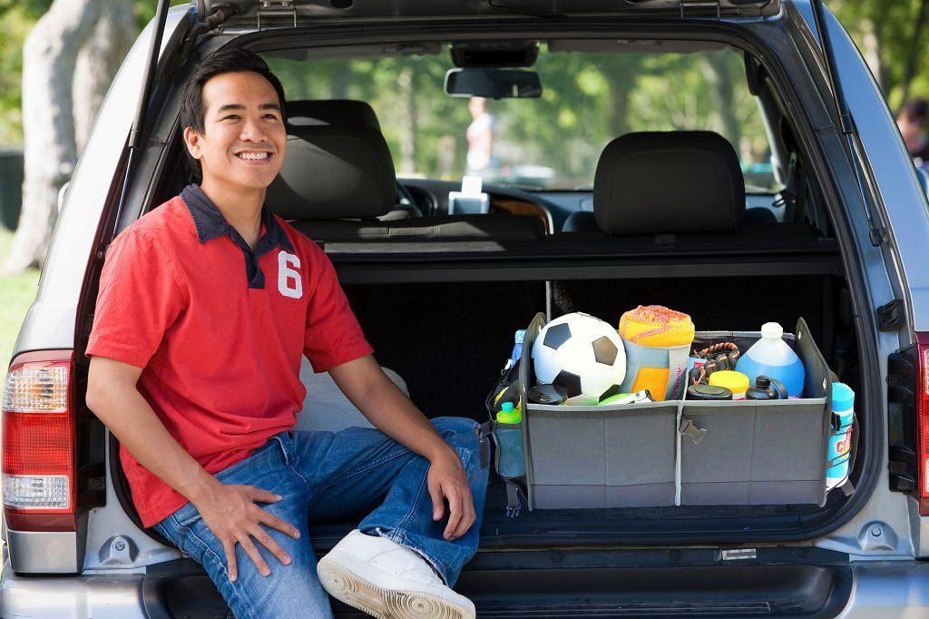 kid sitting in the back of an suv with his sports gear in the trunk organizer