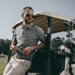 golfer dressed in smart clothes leaning on a golf cart