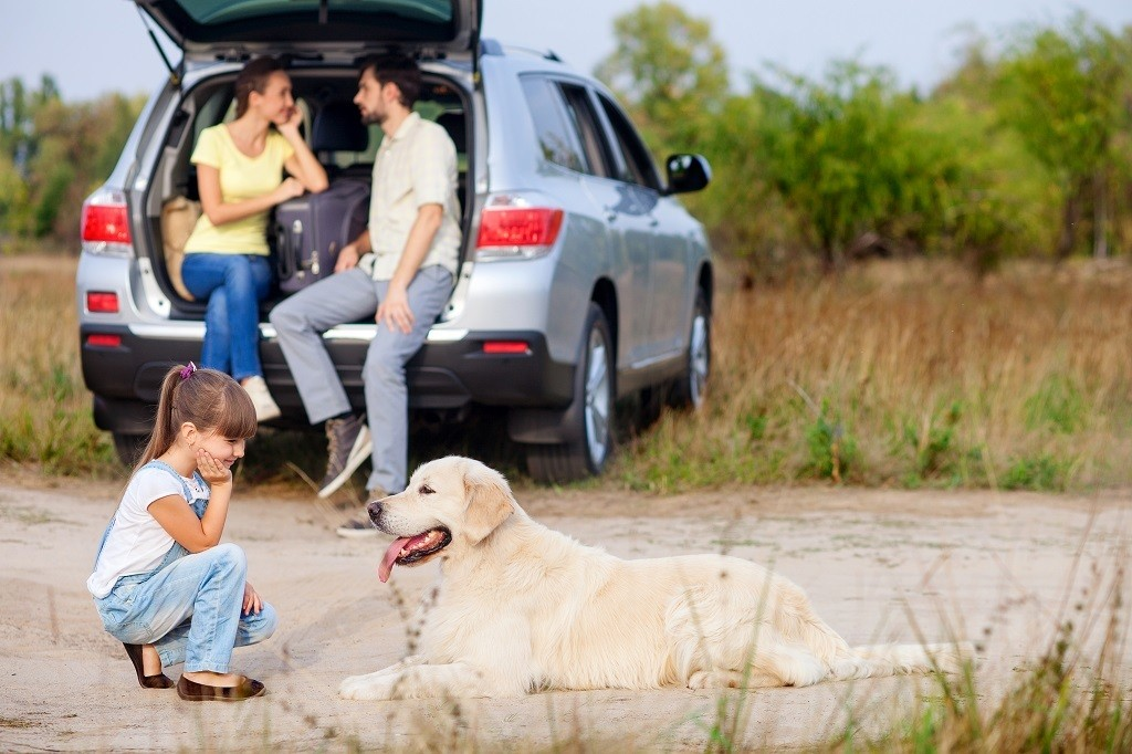 young coupon sitting in the back of their SUV with child and dog in the foreground