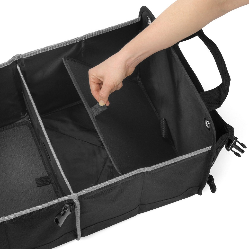 hand lifting up plastic inserts inside the organizer to fold it