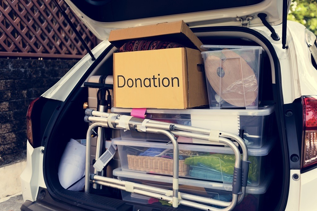 back of car filled with items like donations, a walker, storage boxes and more