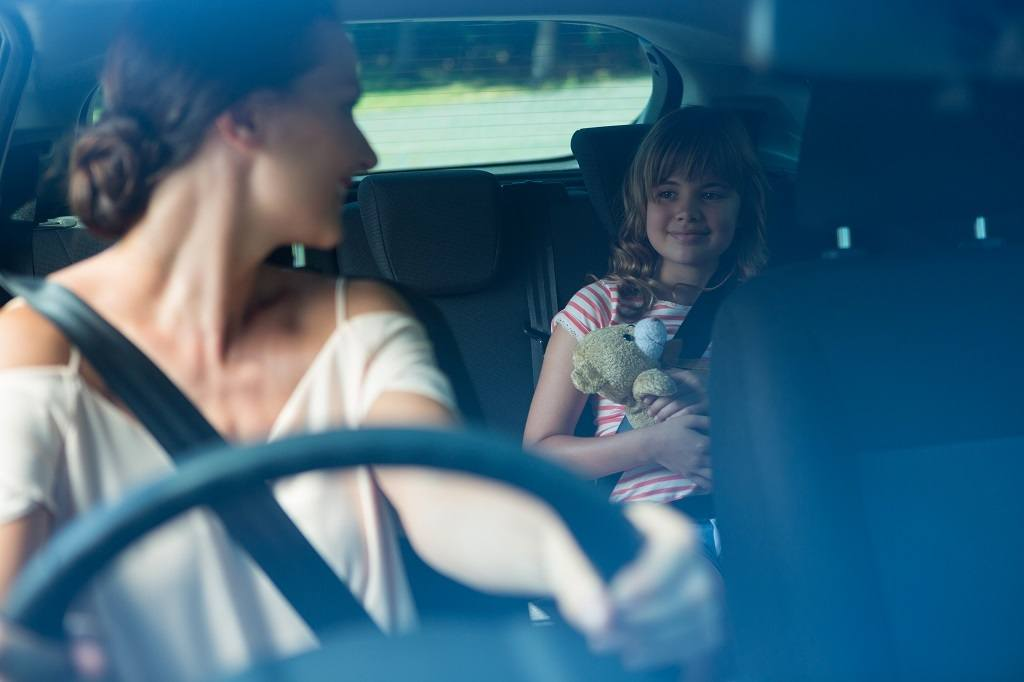 woman looking at her daughter in the backseat while driving